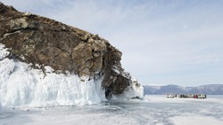 View of the rocky shore of Olkhon island in winter. Blocks of ice, snow and excursion in the distance