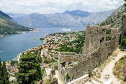 View of the roofs of the houses and the marina with a fortress wall in the old town of Kotor, Montenegro