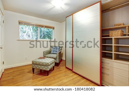 View Of The Room Corner With Chair And Open Slide Doors Wardrobe Cabinet With Shelves Drawers