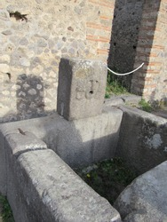View of the ruins of a water fountain with a face sculpture located in Pompeii, Italy
