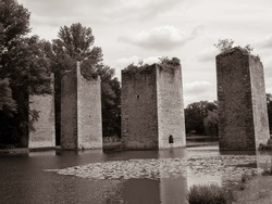 view of the ruins of the old bridge at Lussac Les Chateau in France in black and white