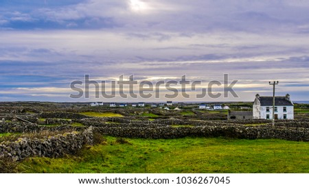 View of the scenery of Inis Mor in Ireland, showing the fields, dry stone walls and traditional farm houses. Taken on an overcast day.