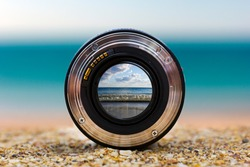 View of the sea surf through a photographic lens lying on a sandy beach on a sunny day.