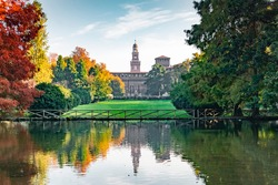 View of the Sforza Castle from Sempione Park (Milan - Italy) in an autumn day with a small lake in the foreground
