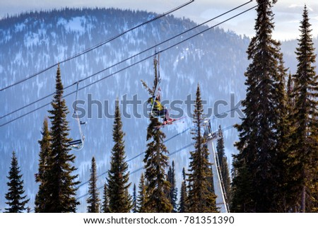 View of the ski lift and snow-capped mountains with coniferous forest in Sheregesh, Russia. Skiers climb the ski lift on a ski lift. #781351390