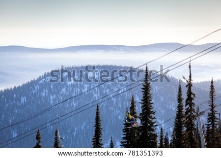 View of the ski lift and snow-capped mountains with coniferous forest in Sheregesh, Russia. Skiers climb the ski lift on a ski lift #781351393