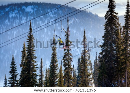 View of the ski lift and snow-capped mountains with coniferous forest in Sheregesh, Russia. Skiers climb the ski lift on a ski lift. #781351396