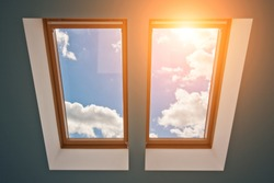 View of the sky and clouds from the window on the roof, sunlight through the attic window, light in the house, skylights