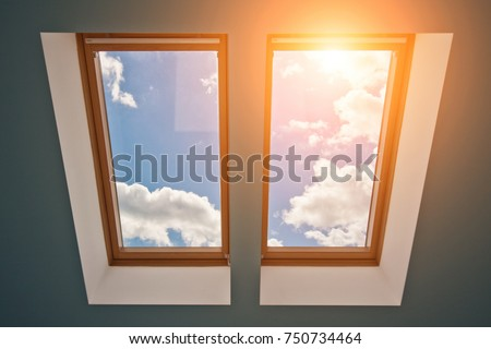 View of the sky and clouds from the window on the roof, sunlight through the attic window, light in the house, skylights \n