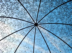 View of the sky through a metal dome construction of gazebo