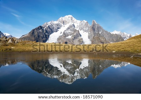 View of the south side of Mont Blanc reflected in a small alpine lake. Val Veny, Italy