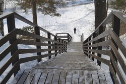 View of the steep descent down the wooden stairs with railings down to the river in the winter park, below comes a lone man along the river
