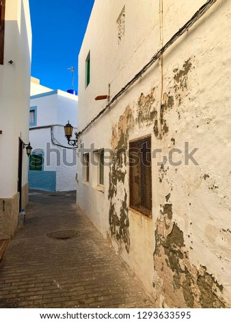 View of the street with white shabby walls of small buildings, architecture buildings with peeling paint, cosy street in fishing town El Cotillo on Atlantic coast  #1293633595
