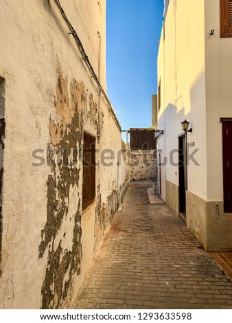 View of the street with white shabby walls of small buildings, architecture buildings with peeling paint, cosy street in fishing town El Cotillo on Atlantic coast  #1293633598