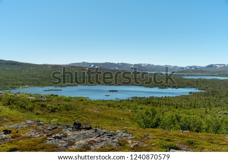 View of the Swedish highlands or fjeld world with mountain peaks and a small lake, on a beautiful summer day with blue sky and sunshine