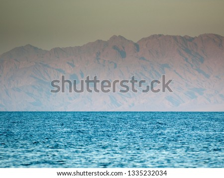 View of the territory of Saudi Arabia through the Gulf of Aqaba from the side of Dahab. Bright blue sea and brown rocks in the distance. #1335232034