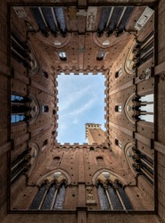 view of the Torre del Mangia and from inside the Cortile del Podestà near the public palace of siena