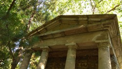 View of the Tuscan order gabled dilapidated temple portico from below. Ancient Greek temple imitation in a park for children. Looking up at the antique portico pediment,entablature,capital,columns.