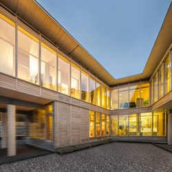 View of the two legs of a sustainable wood office building from the inner courtyard with lighting at night