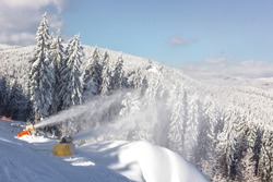 View of the Ukrainian Carpathians. Snow blowers in the ski resort Bukovel. Snowy mountains. Spruce forest. Ski slopes for skiers and snowboarders. Snow blowing mechanism. Sunny frosty weather.