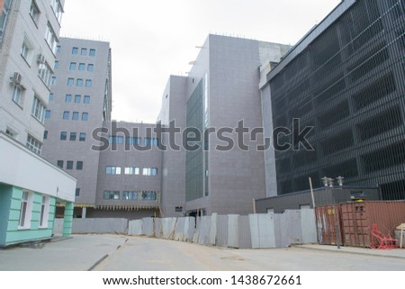 View of the unfinished modern building. The building site is fenced.