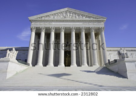View of the United States Supreme Court building with shadow of flag on the steps.