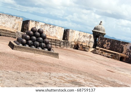 View of the upper interior of El Morro fort located in Old San Juan Puerto Rico.  There is a large pile of cannon balls in a pyramid shape.