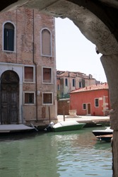 View of the Venetian canal and the old building through the arch. Sunny summer day in italian town. Concept of old Europe south atmosphere