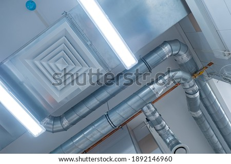 View of the ventilation pipes under ceiling. Ventilation pipes bottom view. Chrome plated pipes from an industrial hood. Concept is an industrial ventilation system. Air purification system