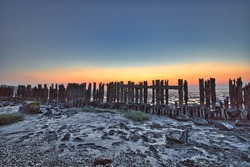 View of the Wadden Sea during sunset, at low tide. Wooden posts as a silhouette in the mud. UNESCO. Wadden Sea World Heritage