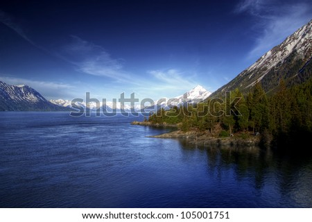 View of the water of the Turnagain Arm near Hope Alaska in soft evening light with bright blue skies.