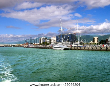 View of the waterfront of Cairns, Australia under blue sky and clouds from the water