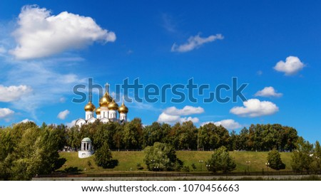View of the white church with golden domes among trees against the blue sky, Yaroslavl, Russia #1070456663