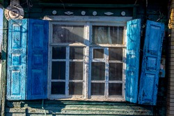 View of the window and colored shutters in an old wooden house, Russia