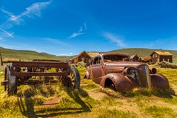 View of the wreck of an old car in Bodie, ghost town. Bodie State Historic Park. Abandoned wooden houses, California, USA.