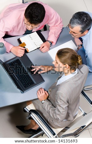 View of three colleagues sitting before laptop around table and looking at its screen
