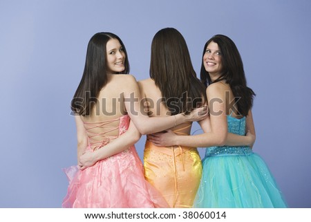 View of three teenage girlfriends holding each other by the waist while wearing prom dresses.