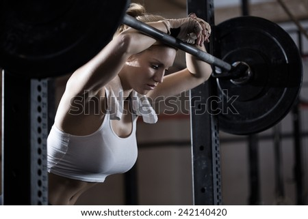 View of tired girl after weight lifting