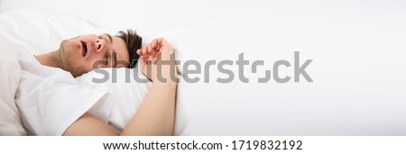 View Of Tired Young Man Snoring While Deep Sleeping In Bed Foto stock ©