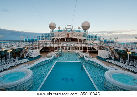 View of top deck of cruise ship with luxurious pools and spa facilities.