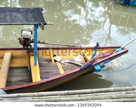 view of traditional indonesian motor speed boat perahu nelayan or dory fishing boat on the river at dock with trees background and reflective sun light clouds on clear blue green water sky vintage