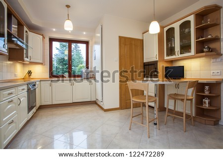 View of traditional kitchen in beige color with television
