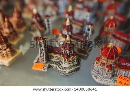 View of traditional tourist souvenirs and gifts from Florence, Tuscany,  Italy with toys, masquerade masks, fridge magnets with text