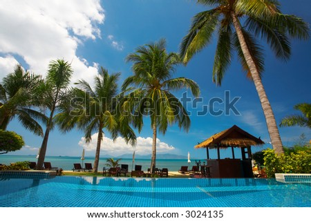 view of  tropical resort swimming pool scene early in the morning - stock photo