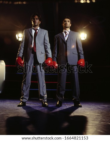 View of two businessmen standing in boxing gloves in the ring