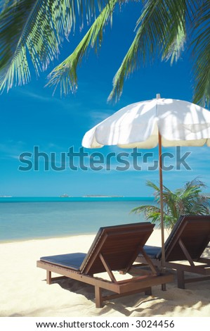 view of two chairs and  white umbrella on the beach