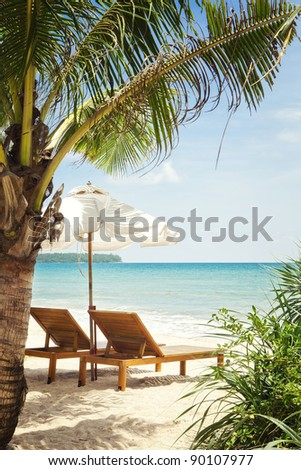 view of two chairs and  white umbrella on the beach #90107977