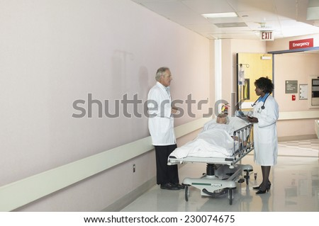 View of two doctors wheeling a patient on a gurney down the hall