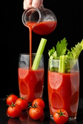 View of two glasses with Bloody Mary cocktail with celery, woman's hand serving from a jug, and cherry tomatoes, on black background, in vertical