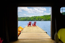 View of two red Adirondack chair on a wooden dock from a cottage's boathouse in Muskoka, Ontario Canada. In the background cottages are nestled between trees.